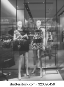 Blurred image of boutique display window with mannequins in fashionable dresses for background.  Black and white image.