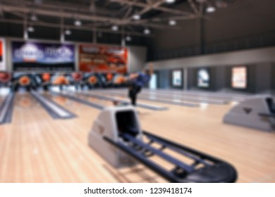 Blurred image of a bowling alley. The athlete throws the ball. Background texture.