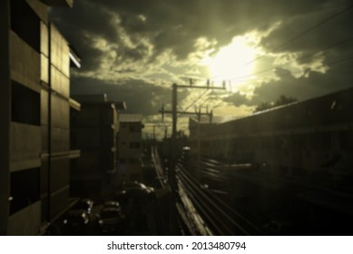 Blurred image of buildings in the city and the atmosphere of the dark sky, dense clouds, light shining from the sun.