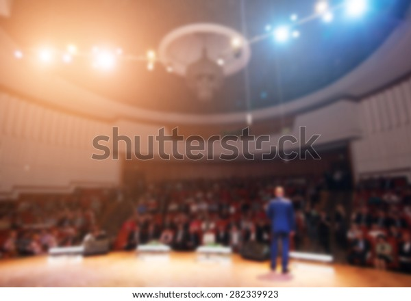 blurred image of a businessman giving a presentation in a conference/meeting