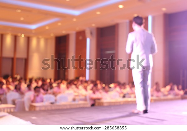 blurred image of businessman giving a speech on the stage