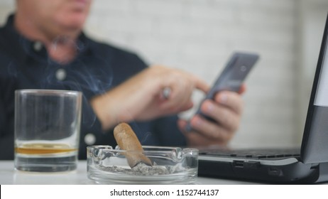 Blurred Image with a Businessman Smoking Cigar Drinking Whisky and Using Cellphone