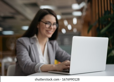 Blurred image of businesswoman using laptop computer, watching training courses, focus on laptop. Beautiful woman freelancer working at workplace, typing, searching on website. Copy space