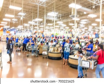 Blurred image busy cashier, line of crowd customers at check-out counter. Payment with credit card to store clerk, employee help to bag groceries. Cashier register, computer, checkout payment terminal