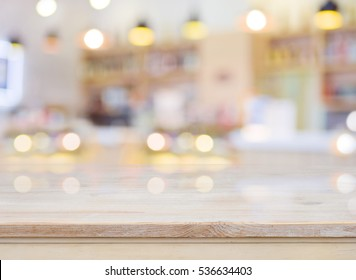 Blurred image of cafe interior with wooden table in front.
