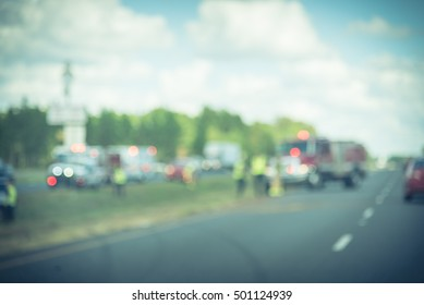 Blurred image car accident on U.S. Highway 59. Fire engines and crews rescue injured victims and clean up debris scattered. Both highway directions are blocked. Insurance theme, vintage filter look.