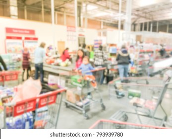 Blurred image cashier with long line of customer at check-out counter of wholesale store in America. Concept of busy shoppers at weekend.