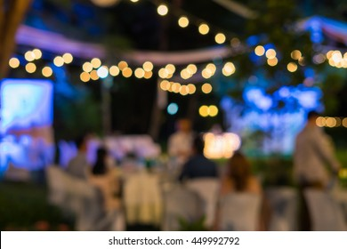 Blurred image of celebrate outdoor wedding party in the garden night time for background usage.