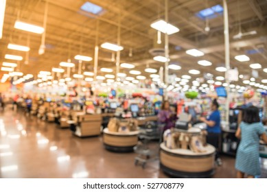 Blurred image check-out counter in local store at Humble, Texas, US. Row of cashier registers, computer payment terminal, checkout store clerks. Customers pay with credit card. Bokeh light background.