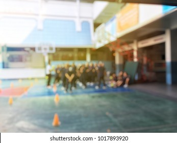 Blurred image of children or male and female students in secondary school are learning football or soccer on school playground in physical education time. Bangkok,Thailand. physical activities concept