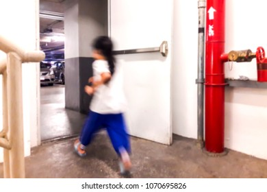 Blurred image of children running out of the fire exit.