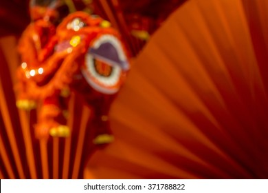 Blurred image of Chinese traditional dancing lion on red background.