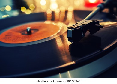Blurred image of Christmas. Turntable vinyl record player. Sound technology for DJ to mix & play music. Vintage vinyl record player on a background of Christmas decorations, cap, wreath and lights