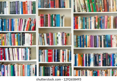 Blurred image of colorful bookshelf In secondhand shop