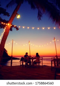 blurred image of couple have romantic dinner at beach with sunset sky background