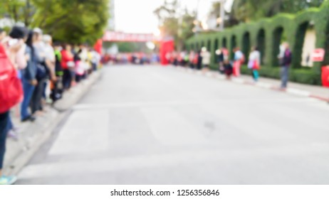 blurred image of crowd people beside the wide road cheer up for the marathon runner at the start point