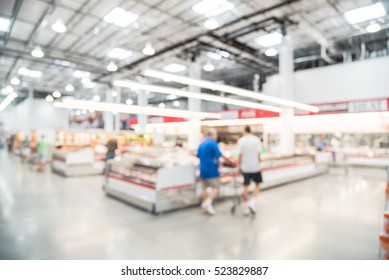 Blurred image customers shopping for fresh raw beef, pork, chicken, fish at meat department in wholesale store in US. Fully loaded shelves with variety of meat slices in boxes in a large supermarket.