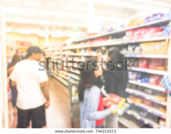 Blurred image customers stock up candy, chewy and gummy goodness for holiday season. Crowed of people buying multipacks, variety packs, chocolate, hard candies, bars, sour at grocery store in America