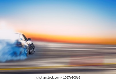 Blurred of image diffusion race drift car with lots of smoke from burning tires on speed track at sunset.