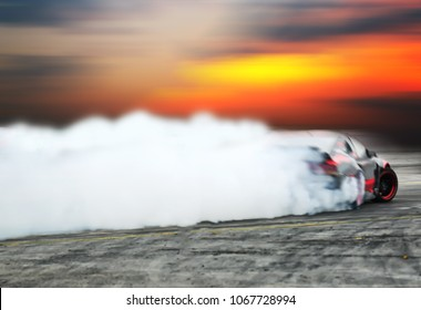 Blurred of image diffusion race drift car with lots of smoke from burning tires on speed track at sunset evening.