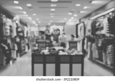 Blurred image of a dress store with customers and dressed mannequins for background. Black and white image.