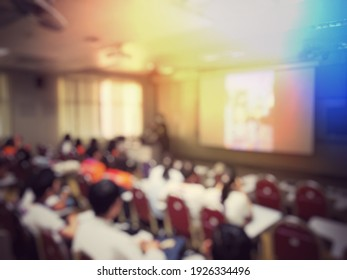 Blurred image of education people and business people sitting in classroom for profession seminar and the speaker is presenting new technology and idea sharing with the content activity.