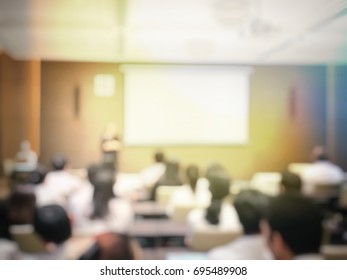 blurred image of education people and business people sitting in conference room for profession seminar and the speaker is presenting with screen projector and idea sharing with the content activity.