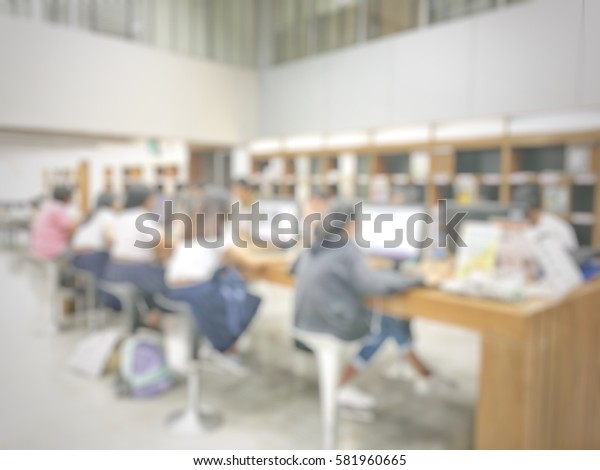 blurred image of education people searching a book and journal from computer in library