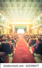Blurred image of event at university hall in Hanoi, Vietnam. Campus lecture hall, full of audience in line of red armchairs row seats and balcony. International conference meeting room. Vintage tone