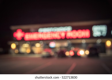 Blurred image exterior emergency room with neon led sign illuminated at night in Houston, Texas, US. Facade of emergency department neon shining signboard. Healthcare service concept. Vintage filter.