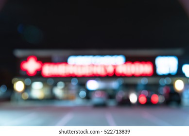Blurred image exterior emergency room with neon led sign illuminated at night in Houston, Texas, US. Facade of emergency department with neon shining signboard and car park. Healthcare service concept
