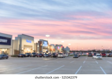 Blurred image exterior view of empty parking lots in modern shopping center in Humble, Texas, US at sunset. Mall complex outdoor uncovered parking and bokeh light of retail store in background.