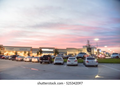 Blurred image exterior view of modern shopping center in Humble, Texas, US at sunset. Mall complex with row of cars in outdoor uncovered parking lots and bokeh light of retail store in background.