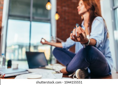 Blurred image of female student meditating on desk in classroom calming mind with her hand in focus