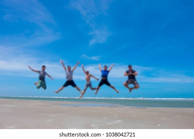 blurred image of five energetic people jumping at the beach gang playing on beautiful summer beach while vacation at the popular beach for tourists (Amazing landscape ocean), in space for text
