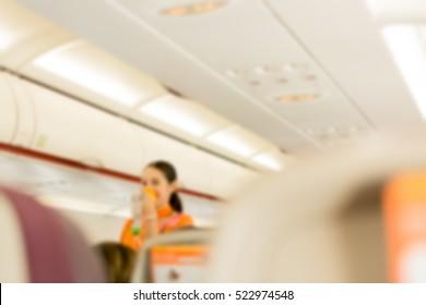 blurred image of flight attendants during Pre-flight safety demo