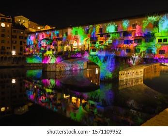 Unscharfes Bild.Florenz am Abend. Farbige alte Brücke oder Ponte Vecchio, bekannt als Vasari-Korridor, Nahaufnahme. Weihnachten- und Neujahrsfest. Malerische, mittelalterliche Bogenbrücke über den Fluss Arno
