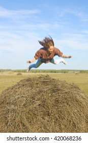 blurred image. girl jumping and fallen down on straw stack. woman against blue sky with clouds.