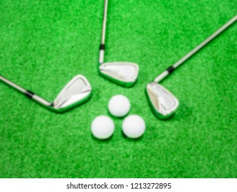 Blurred image of golf clubs and balls placed on artificial grass.