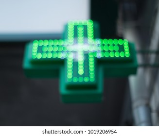 Blurred image of the green medical cross of the pharmacy symbol. Background picture with space for text.