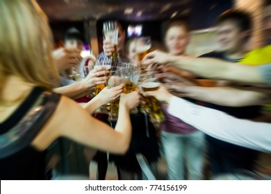 Blurred image. Group of best friends toasting with beers at cafe bar restaurant - Teenagers having fun eating pizza together at lunch time - Concept of friendship and togetherness