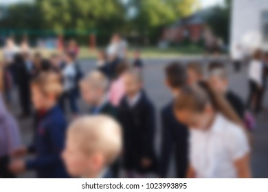 Blurred image. A group of children near the school.
