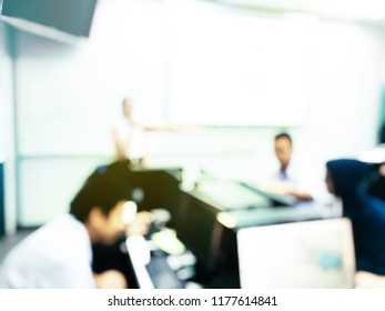 Blurred image of group of students are learning and sitting at desk using computer lap together in classroom for study and workshop in computers room at secondary school. education technology concept.
