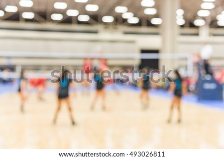 Blurred image group of teen girls playing indoor volleyball. Volleyball competition blur background. High school volleyball tournament concept.