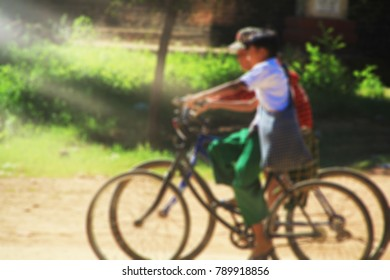 Blurred image of happy 2 Asian students ride a bicycle  in the road countryside.