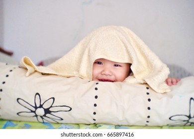 Blurred image of Happy Cute Asian little kid playing hide and seek under blanket on the bed