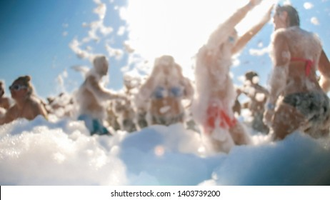 Blurred image of happy people dancing on the soap foam party. Crowd enjoying and having fun on the disco at sea beach