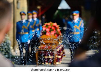 Blurred image of honor guard standing by a coffin at a funeral