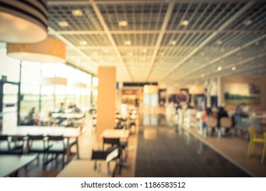 Blurred image large cafeteria, canteen, food court at shopping mall or corporate in Texas, USA. Defocused modern public dining area natural lights from windows for background use, customer eating