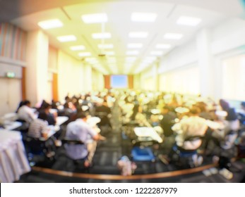 Blurred image of large examination room with students sitting on lecture chair doing final exam, studying, learning, doing final test in exam hall in university or campus. Education concept.